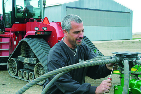 The recent rains have made farmers happy and given Glen Crawford, who farms north of Aberdeen, time to replace a hose on his air seeder. American News Photo by Jeff Natalie-Lees
