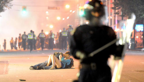 Riot police walk in the street as a couple kiss in Vancouver after riots broke out after game seven.