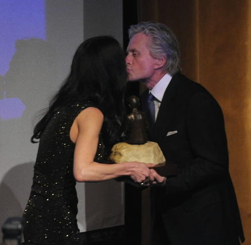 Actor Michael Douglas is presented the Monte Cristo award by wife, actress Catherine Zeta-Jones, during the 12th Annual Monte Cristo Awards at The Edison Ballroom on April 16  in New York City.