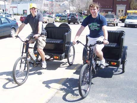 Josh Lycka (left) and Calvin Schemanski sit on pedicabs in May 2009, around the time they launched their Petoskey Pedicab business.