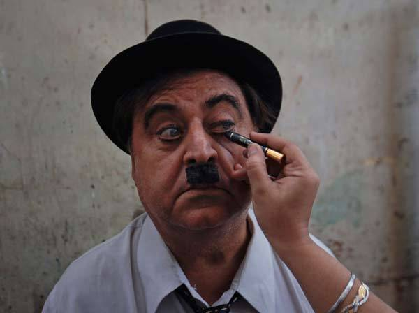 Ashok Aswani, a 63-year-old doctor, has his make-up applied as he gets dressed up for Charlie Chaplin's birthday celebrations in India. Aswani formed the Charlie Circle fan club after watching Chaplin's Gold Rush in 1973. Every year Aswani celebrates Chaplin's birthday on April 16 by taking a walk along with a group of Chaplin impersonators through the city streets, which is followed by other cultural programs dedicated to Chaplin. Aswani who is an Ayurvedic doctor, sometimes gives away free Chaplin CDs with his potions to cheer his patients up.