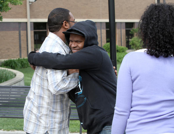 LaVar Bridgwater, left, son of murder victim Melissa Bridgewater, embraces Jerry Hudson Jr., the son of the man who killed his mother. Both families grew up together. Jerry Hudson was sentenced to 60 years in prison for shooting his ex-wife to death outside an Oak Brook hotel early on New Year's Day 2010.