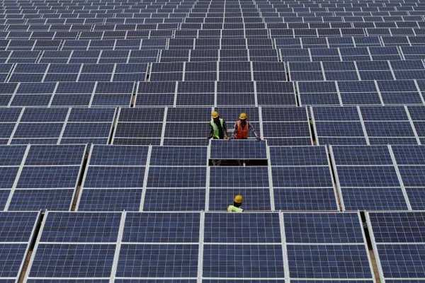 Indian workers install solar panels.