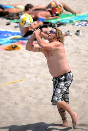 Ronnie Cope of West Palm Beach returns a serve during a volleyball game on Lake Worth beach. Despite calmer winds, there is a moderate risk of rip currents at the beaches.