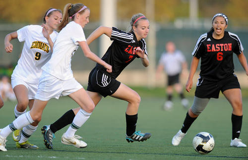 Easton's Caitlin Lucas (7) center, dribbles away from the Emmaus High School defenders during their soccer game Tuesday night.