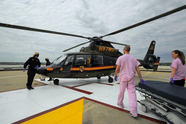 Garrick Anderson and Valerie Smith meet a state police medevac helicopter that lands on the pad of the University of Maryland Shock Trauma with a patient Tuesday, April 17, 2012.