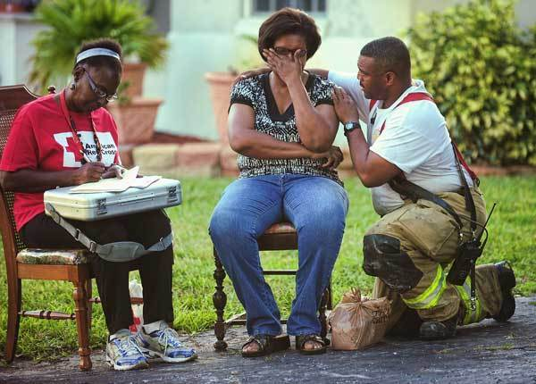 Joan Morales is comforted by Pembroke Pines firefighter George Lindor after her dog was killed in a fire at her home.