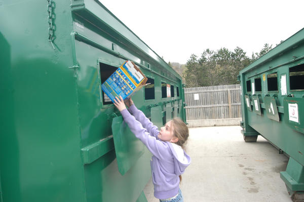 Abi Thompson, 9, of Boyne City, drops a cardboard box into a recycling bin at the Charlevoix County recycling site in Boyne City. A new attendant works there for two hours on five days per week to help recyclers compress their cardboard, so the county can pay for fewer bins to be hauled away, officials said.