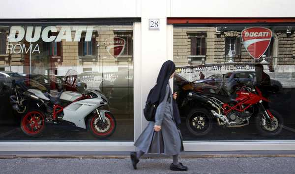 A nun passes a Ducati motorcycle store in Rome. Volkswagen AG's Audi has announced that it will purchase the Italian motorcycle maker from owner Investindustrial.