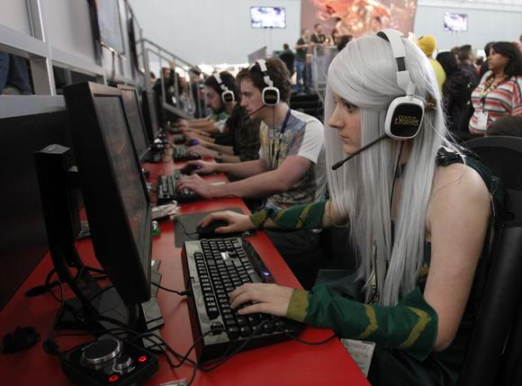 A girl dressed in costume plays a video game at the PAX East gaming conference in Boston.