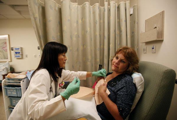 Nurse Harumi Mankarios examines Tina Roark, a patient with advanced breast cancer.