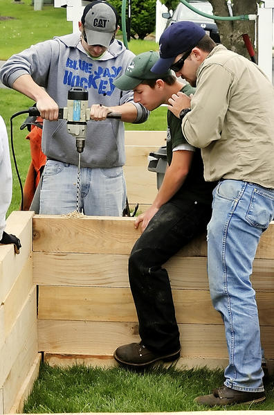 Penn State Mont Alto students, from left, Mike Harbart, Andrew Teets and Adam Wentzel build a planting bed at Quincy Village in Quincy, Pa.