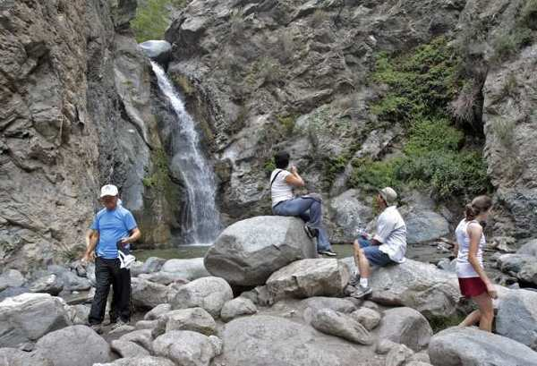 Hikers take in the sights at Eaton Canyon Falls in the Eaton Canyon Natural Area north of Pasadena in the Angeles National Forest. Officials of Tuesday advised hikers not to trek to the second waterfall.