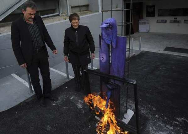 Antonio Manfredi, director of the Casoria Contemporary Art Museum, and Italian artist Rosaria Matarese burn one of Matarese's creations in front of the museum on Wednesday.