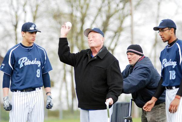 Longtime Petoskey Little League volunteer Duane Hasse (center) throws out the ceremonial first pitch before the Petoskey High School baseball home opener Wednesday at Turcott Field. Joining Hasse are Northmen players Joe Robbins (8) and Jordon Smith (18), and his son, Brad.
