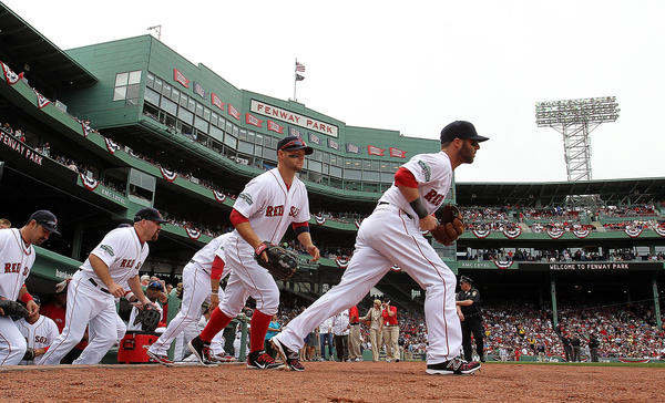 Dustin Pedroia of the Boston Red Sox leads his team onto the field against Tampa Bay Rays at Fenway Park April 15, 2012 in Boston, Massachusetts. Both teams wore the number 42 in honor of Jackie Robinson Day.