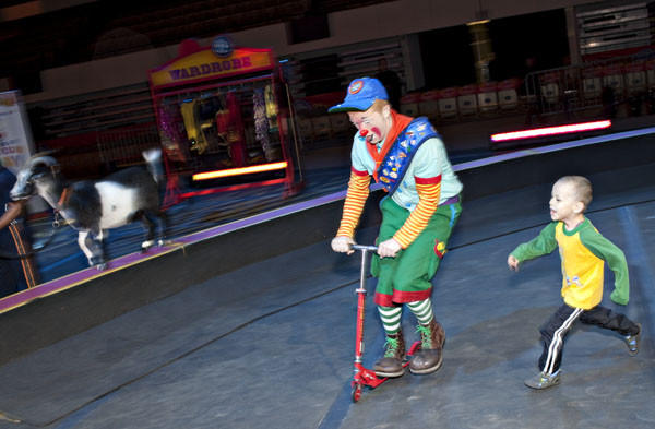 Alex Barney, center, a member of Clown Alley, rides a scooter of Stas Ivanichok, 6,  who chases Barney, as they spend time to wait for a pre-show of Ringlins Bros. and Barnum & Bailey at Hampton Coliseum on Wednesday. The show at the coliseum will continue till this coming Sunday, April 22.