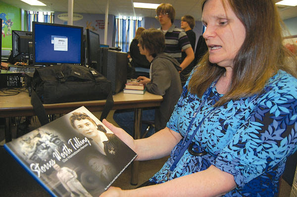 Boyle County High School teacher Susan Michael holds a book her Student Technology Leadership Program students published this year. It is based on interviews with area veterans.