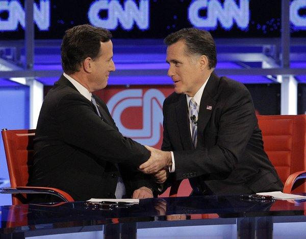Rick Santorum and Mitt Romney talk following a Republican presidential debate Wednesday, Feb. 22, 2012, in Mesa, Ariz.