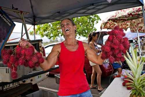 Farmer Jaude Huber shows off her freshly grown rambutan fruits for sale at the Kapaa Farmers Market.