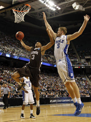 C.J. McCollum #3 of the Lehigh Mountain Hawks goes up for a dunk over Mason Plumlee #5 of the Duke Blue Devils in the second half during the second round of the 2012 NCAA Men's Basketball Tournament at Greensboro Coliseum on March 16, 2012 in Greensboro, North Carolina.