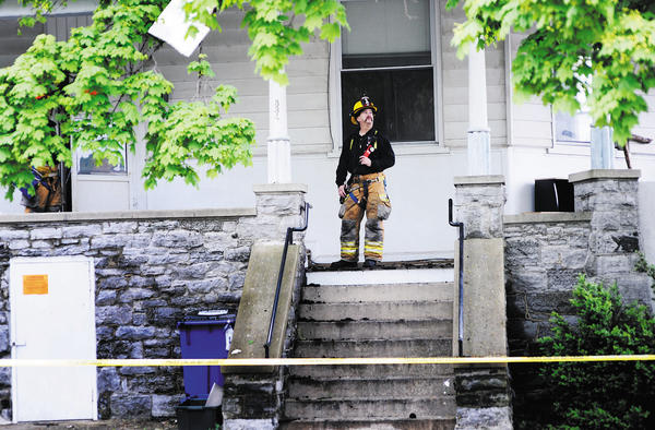 Firefighter Bob Maurer exits 334 Summit Ave. The property is blocked off Thursday for investigations after a Wednesday afternoon fire.