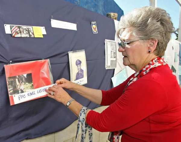 Camille Levee puts a photo of her husband up on the remembrance wall during the First Annual Veteran's Memorial Program at Wellness Works in Glendale. Levee is stepping down from her role as executive director of Glendale Healthy Kids.
