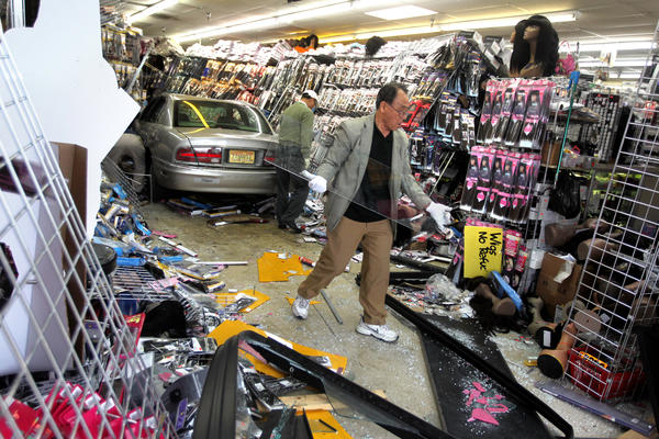 A store worker saves a piece of glass inside the damaged C J Beauty Supply at Chicago and Kedzie in Chicago after a car crashed through the front window of the store on Thursday, April 19, 2012.