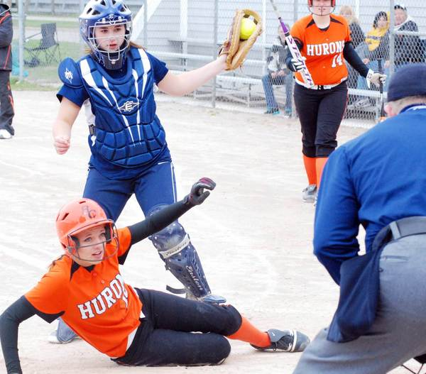 Petoskey catcher Erin Rautio (top) shows the ball to the home plate umpire after tagging out a Rogers City baserunner attempting to score Thursday during a non-league softball doubleheader at Ed White Field.