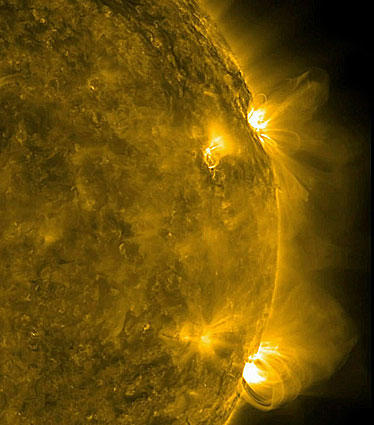 A NASA photo shows a pair of active regions on the sun put on a show as seen in extreme ultraviolet light taken from a Solar Dynamic Observatory spacecraft on Feb. 7. The magnetic field lines above the regions produced fluttering arcs as well as a couple of flares.