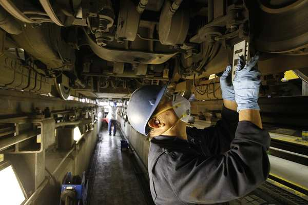 Thi Vu installs new friction brake shoes on one of the Blue Line cars.