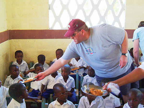 Father Marty Nocchi, pastor of St. Ann, passing out lunch plates to Haitian children.