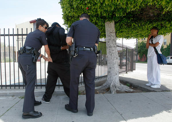 "LAPD Officers Catherine Durant and Tim Wunderlich search a man who was handcuffed for grabbing a woman, right, against her will on Broadway in South Los Angeles. He wasn't arrested because the woman didn't want to press charges. In 1992, the thugs who attacked white trucker Reginald Denny pelted black officers with racial slurs. ""They were calling them Uncle Toms, traitors, all that stuff. They had it harder than we did,"" Wunderlich said, ""because they were on the side of the 'enemy.' """