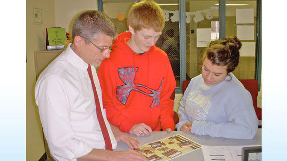 Holt, pictured here with high school students Cameron Nickert and Taylor Chamberlan, has been an administrator with Johannesburg-Lewiston Area Schools for 14 years.