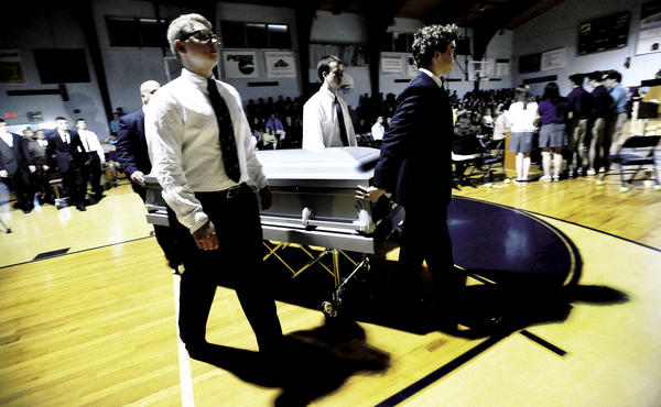 St. Maria Goretti Junior Prom Committee members roll a casket onto the Gymnasium floor during a mock funeral held as part of their Prom Promise campaign.