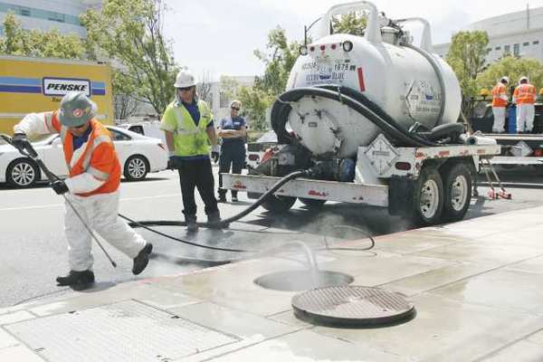 Ocean Blue Enivronmental Services, Inc. workers clean up the disinfected are on Alameda Avenue near the Buena Vista Street intersection in Burbank on Wednesday. A truck was delivering diesel fuel and appeared that his shaft hit a fuel line and leaked.