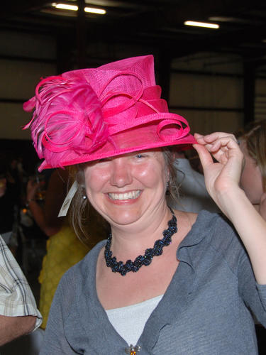 Laura Sheehan tries on a hat for sale at the Run for the Glitz silent auction Friday night.