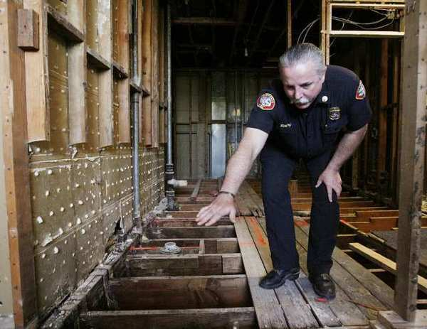 Battalion Chief Greg Godfrey of the Glendale Fire Department shows where the flooring of the shower room was in pretty bad shape and in need of repair at Fire Station 26 in Glendale. The room Chief Godfrey is in will eventually be three bathrooms. The station, which shares the building with the Glendale Public Library, is being updated for $300,000.