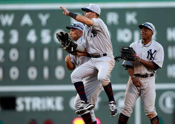New York Yankees right fielder Nick Swisher (33) celebrates with right fielder Raul Ibanez (27) while center fielder Curtis Granderson (14) watches after they defeated the Boston Red Sox 6-2 at Fenway Park.