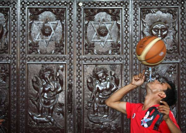 Thaneshwar Guragai spins a basketball on a toothbrush while holding the toothbrush in his mouth for exactly 22.41 seconds to break the last Guinness record of 13.5 seconds set by Thomas Connors of U.K, in Kathmandu.