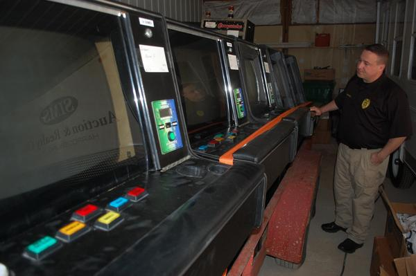 Harrodsburg police Lt. Chad Powell looks over the video gaming machines that were confiscated last month from Pioneer Market.
