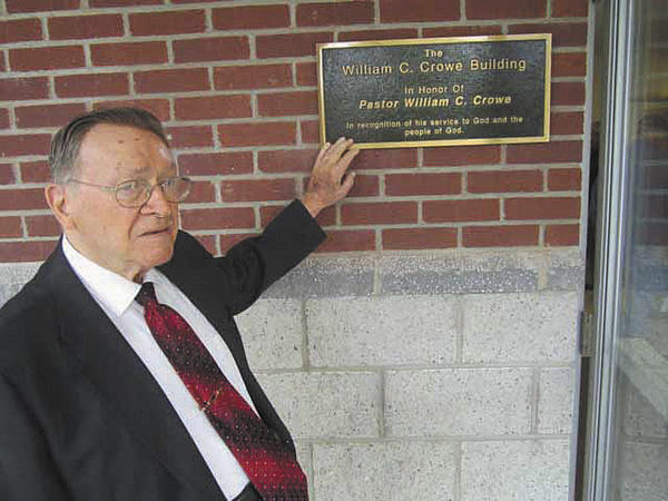 The Rev. William C. Crowe, superintendent of the Martinsburg (W.Va.) Union Rescue Mission since 1961, stands Saturday next to a bronze plaque that names the missions new building in his honor.