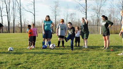 Coaches, buddies and players of the North Star AYSO VIP soccer program work on kicking the ball toward the goal Thursday.