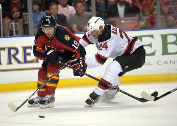 Florida Panthers Scottie Upshall tries to skate around New Jersey Devils Bryce Salvador during the second period.