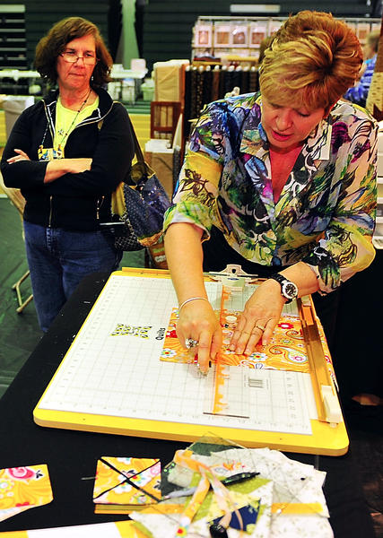 Barbara Dann, right, demonstrates a fabric cutting system Saturday to Jacqueline Bryson of Sharpsburg at the Mason Dixon Quilt Show held at Hagerstown Community College.