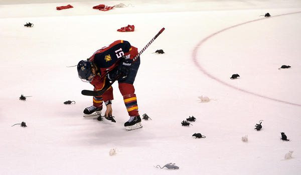 Florida Panthers Brian Campbell picks up a rat to carry off of the ice after the Panthers beat the New Jersey Devils 3-0