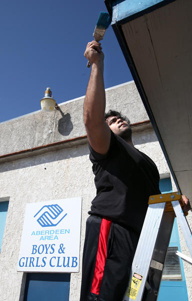 Northern State University football player Robert Johnson stretches to apply a coat of paint on the trim over a door to the Aberdeen Area Boys and Girls Club during Saturday's Day of Champions event.