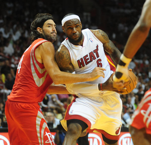Miami Heat LeBron James bulls past  Houston Rockets Luis Scola during the first quarter of the last home game, Sunday, April 22, 2012 at the