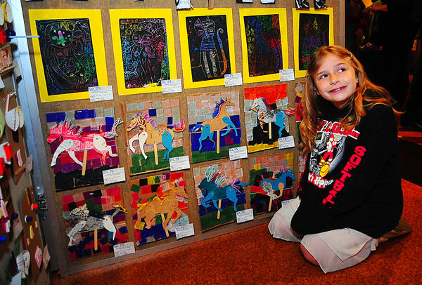 Winter Street Elementary School second-grader Amber Kegarise poses in front of classmates artwork Sunday at the Washington County Museum of Fine Arts. Two of Amber's creations are hanging behind her.