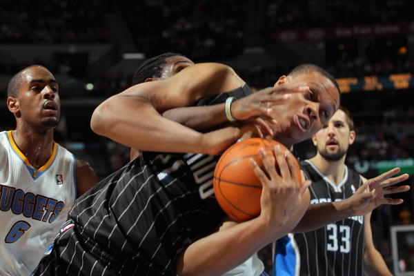 Daniel Orton #21 of the Orlando Magic grabs a rebound and gets taggled up with Kenneth Faried #35 of the Denver Nuggets at Pepsi Center on April 22, 2012 in Denver, Colorado. The Nuggets defeated the Magic 101-74.